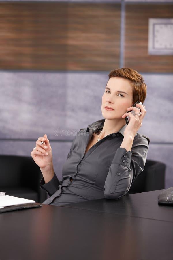 Verticale de femme d'affaires sérieuse au téléphone images libres de droits