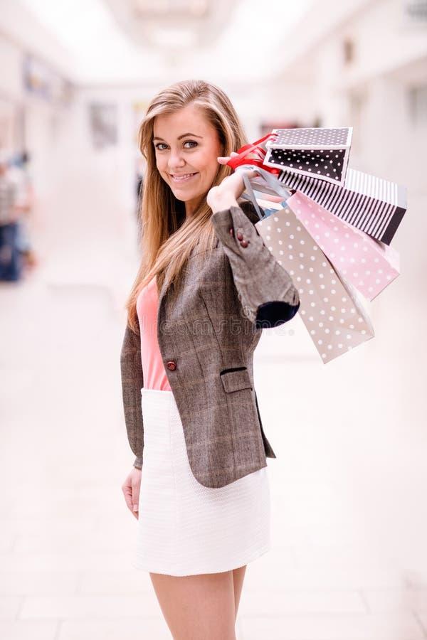 Verticale de femme heureuse retenant des sacs à provisions photos stock