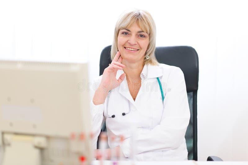 Verticale de femme mûr heureux de docteur au laboratoire photographie stock