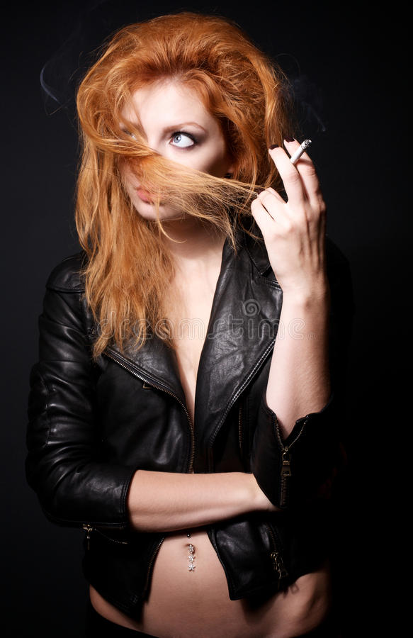Verticale de femme rousse avec une cigarette photographie stock libre de droits