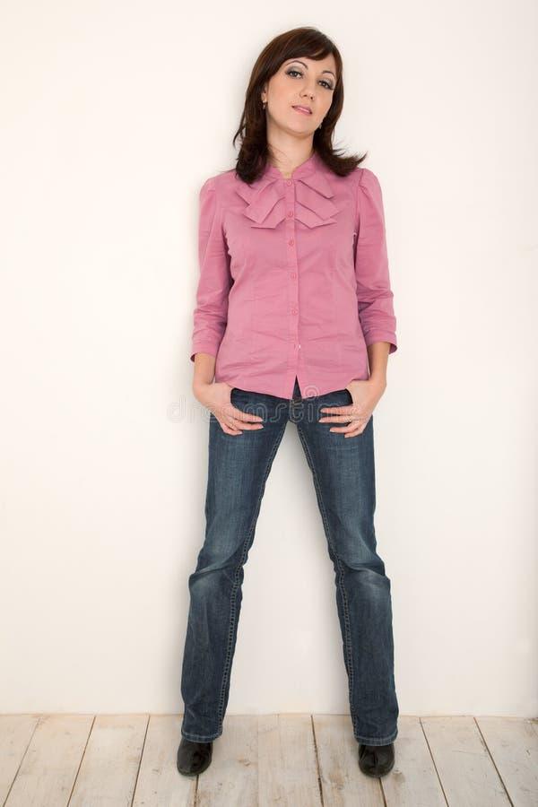 Verticale de fille dans la chemise et des jeans à la pleine taille photographie stock libre de droits
