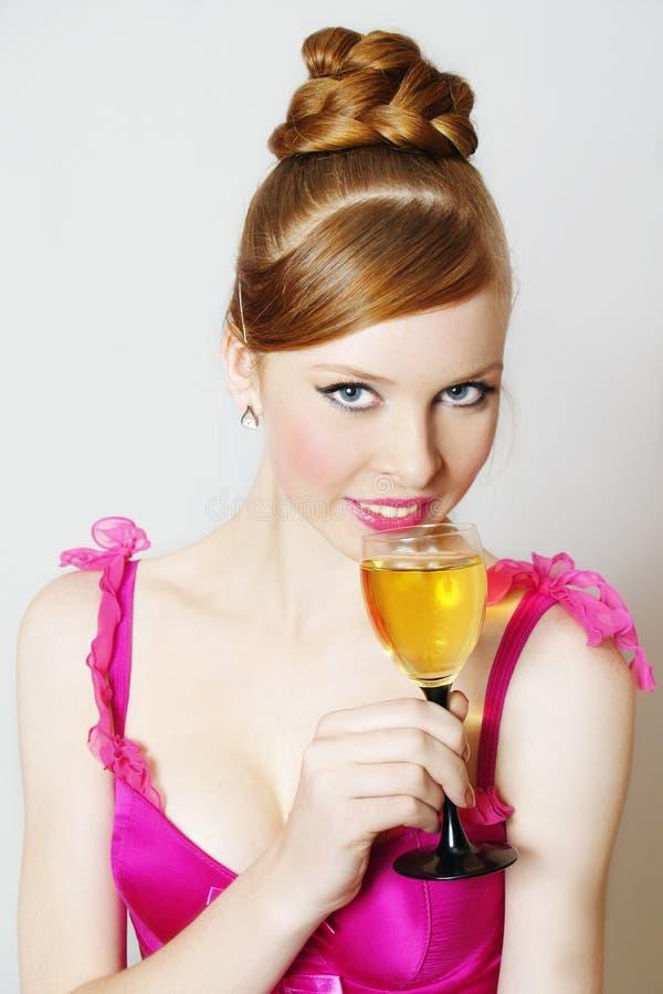 Verticale de fille de roux avec du vin en verre images stock