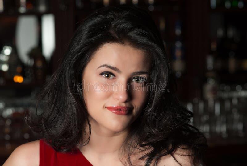 Verticale de fille de sourire de brunette à un bar photographie stock libre de droits