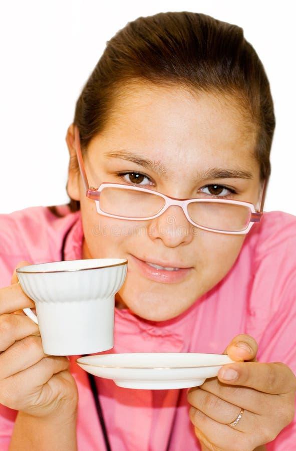 Verticale de fille. La fille boit du thé orange photographie stock