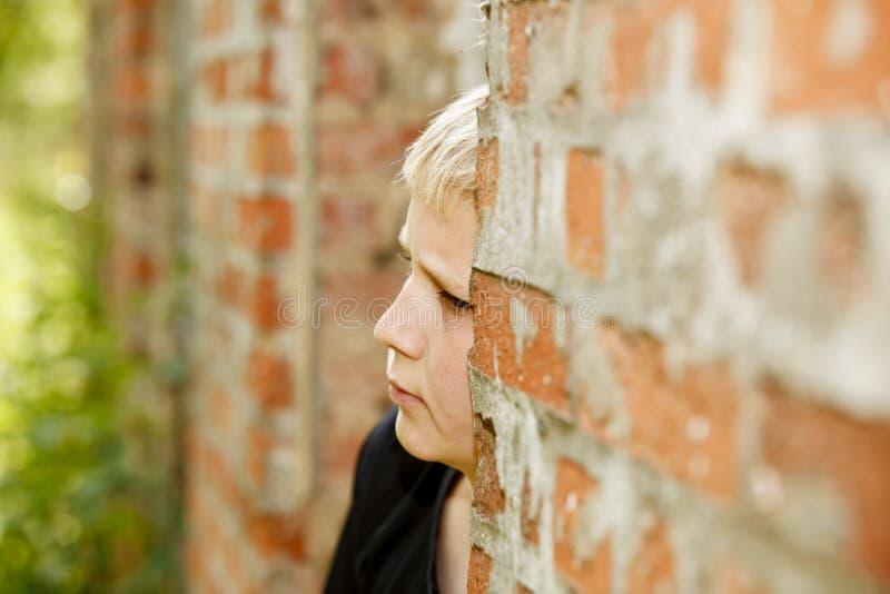 Verticale de garçon au vieux mur de briques images stock