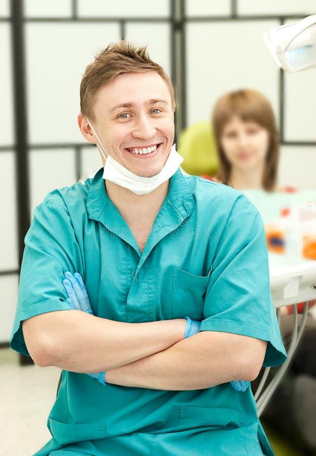 Verticale de jeune dentiste heureux dans sa chirurgie image stock