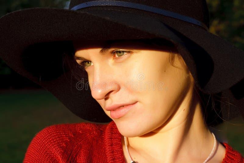 Verticale de jeune femme dans le chapeau noir photo stock