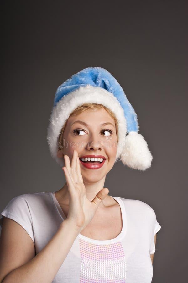 Verticale de jeune femme de sourire dans le chapeau de Santa photographie stock