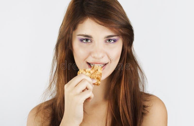 Verticale de jeune femme mangeant le biscuit photo stock