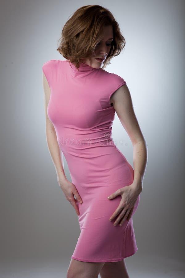 Verticale de jeune femme sexy dans la robe rose photographie stock
