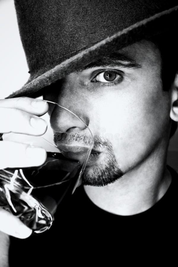 Verticale de jeune homme avec la glace de whiskey photographie stock
