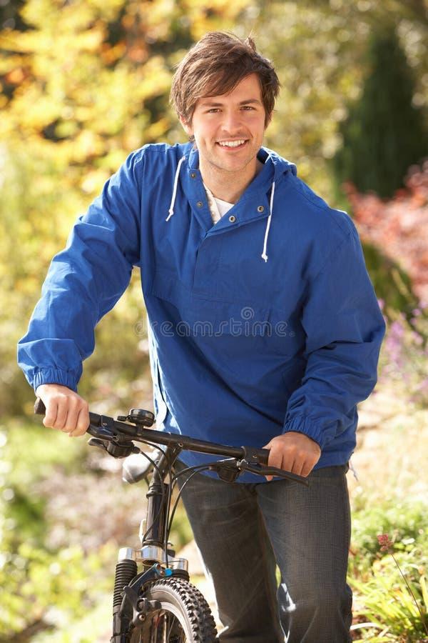 Verticale de jeune homme avec le cycle en stationnement d'automne images stock