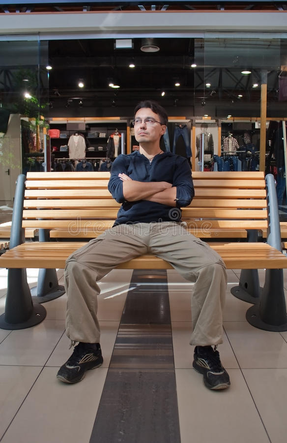 Verticale de jeune homme sur le banc dans le mail photos stock