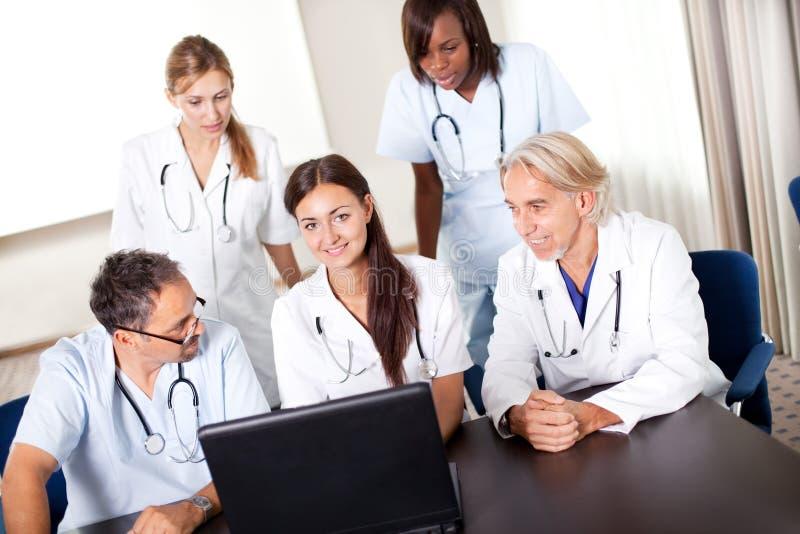 Verticale de jeunes médecins mûrs travaillant ensemble images libres de droits