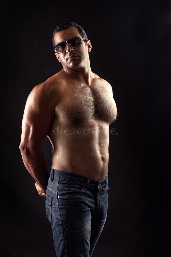 Verticale de l'homme sportif de torse nu posant au-dessus du noir images libres de droits