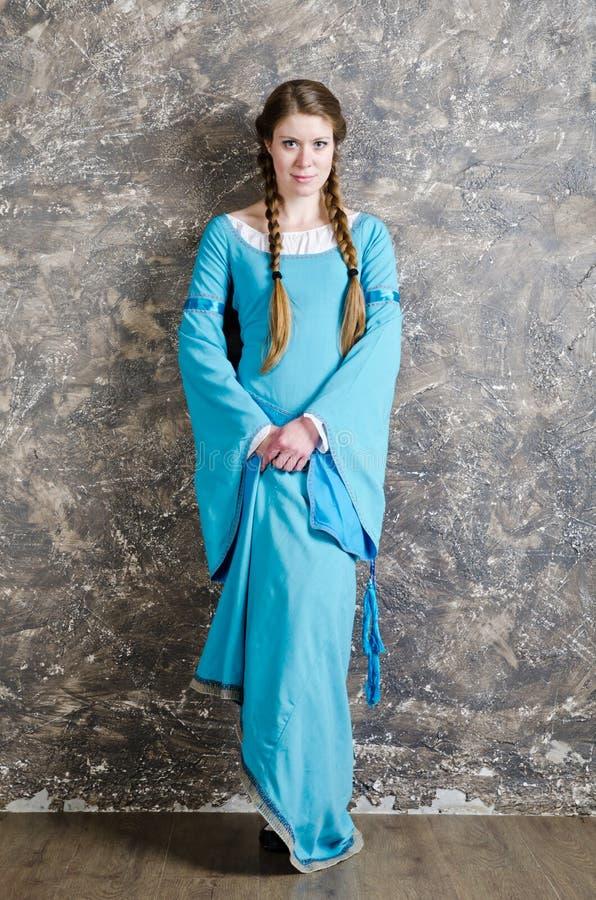Verticale de la femme assez jeune dans la robe bleue photo stock