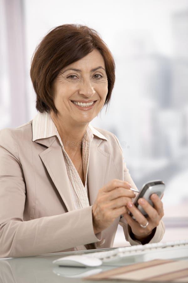 Verticale de la femme d'affaires aînée utilisant le pda images stock