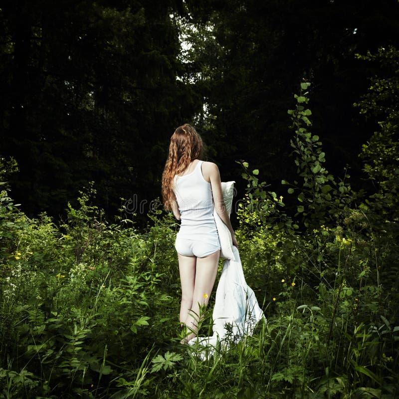 Verticale de la jeune femme en bois mystérieux image libre de droits