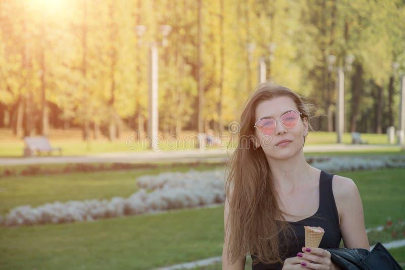 Verticale de la jeune femme heureuse mangeant de la glace photos libres de droits