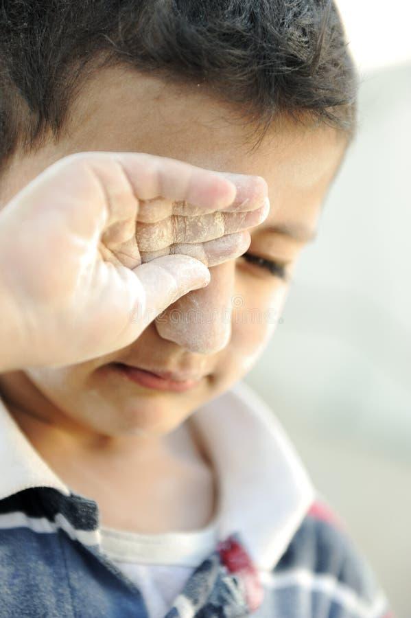Verticale de la pauvreté, petit pauvre garçon, pleurant image libre de droits