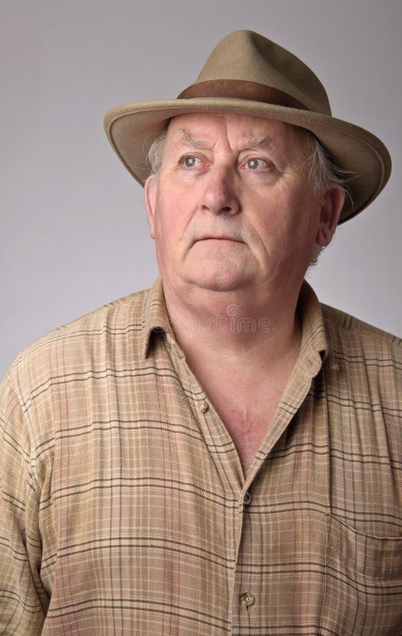 Verticale de mâle aîné utilisant un chapeau photos libres de droits