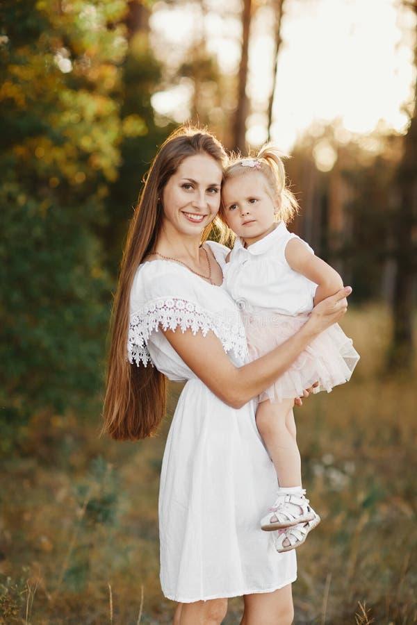 Verticale de mère et de descendant La mère tient une petite fille dans des ses bras sur le fond d'un pré images stock