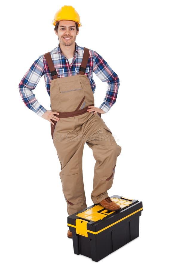 Verticale de mécanicien restant sur la boîte à outils photographie stock