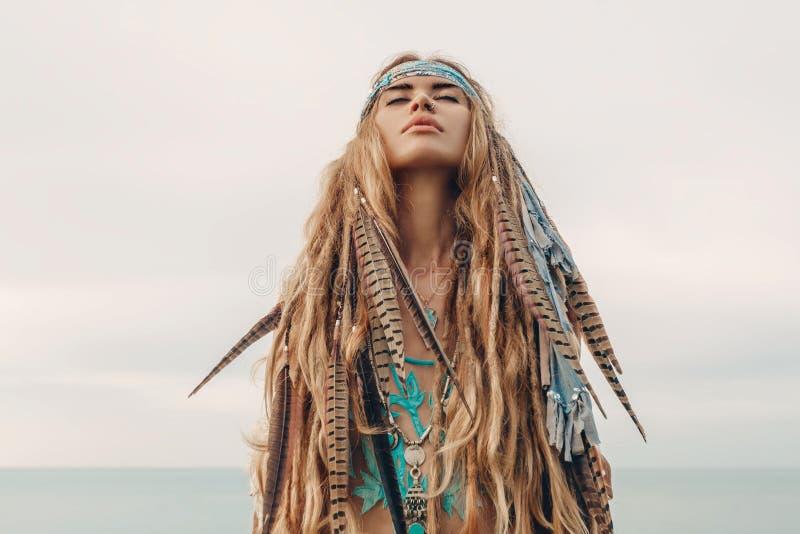 Verticale de modèle de mode à l'extérieur jeune femme de style de boho avec la coiffe faite de plumes photo stock