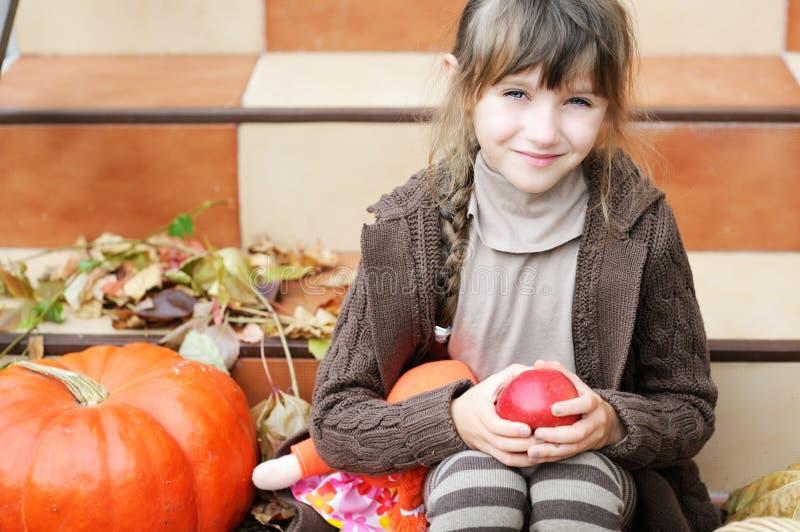 Verticale de petite fille avec la pomme et le potiron photo libre de droits