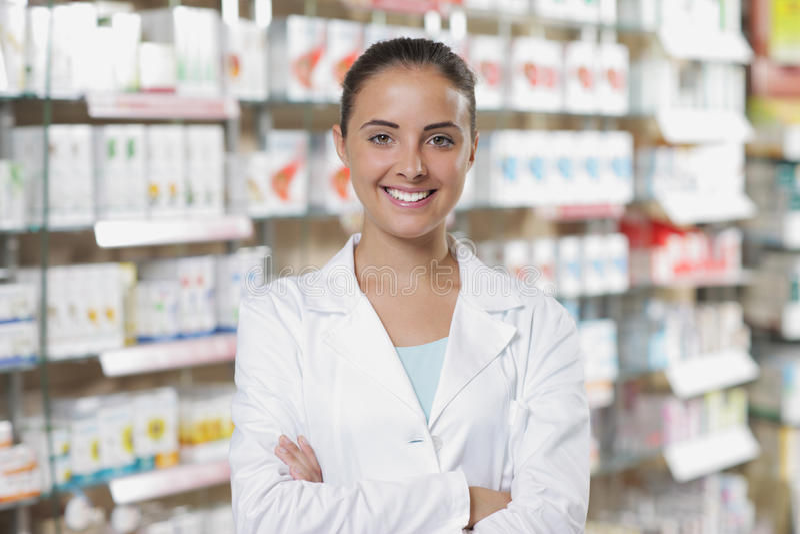 Verticale de pharmacienne de sourire de femme dans la pharmacie image stock