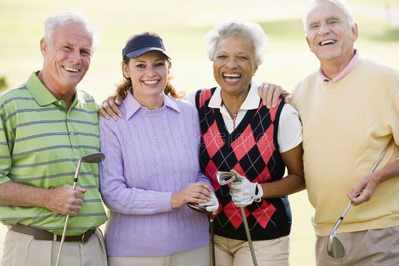 Verticale de quatre amis appréciant un golf de jeu photographie stock libre de droits
