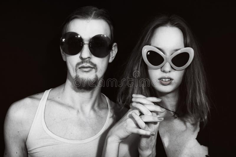 Verticale de studio d'un jeune des lunettes de soleil s'usantes couple images libres de droits