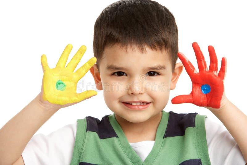 Verticale de studio de jeune garçon avec les mains peintes images stock