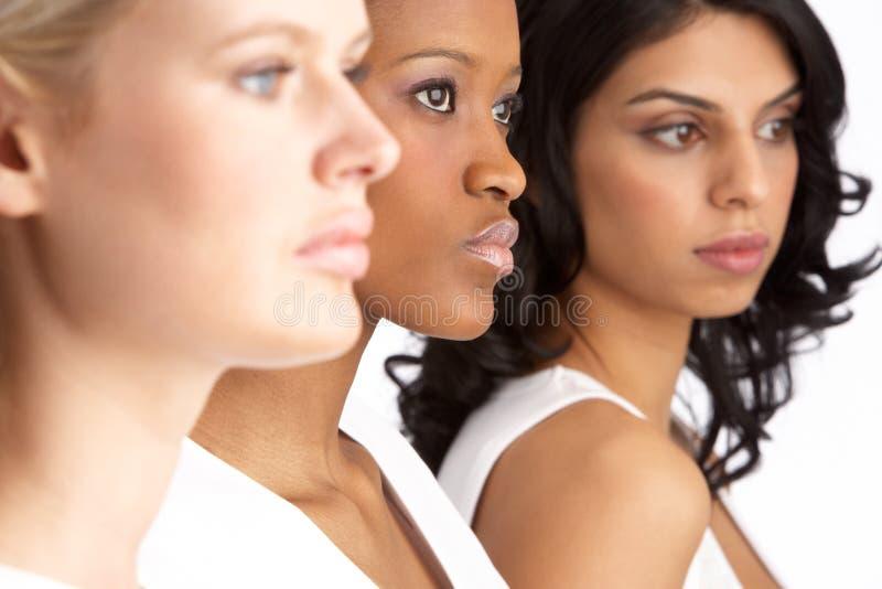 Verticale de trois jeunes femmes attirants dans le studio photo libre de droits