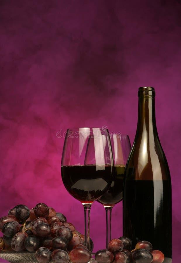 Verticale della bottiglia di vino con i vetri e l'uva immagine stock