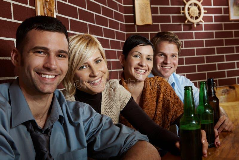 Verticale des jeunes heureux dans le pub photographie stock libre de droits