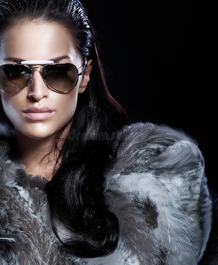 Verticale des lunettes de soleil s'usantes de femme de brune et de la belle fourrure photographie stock