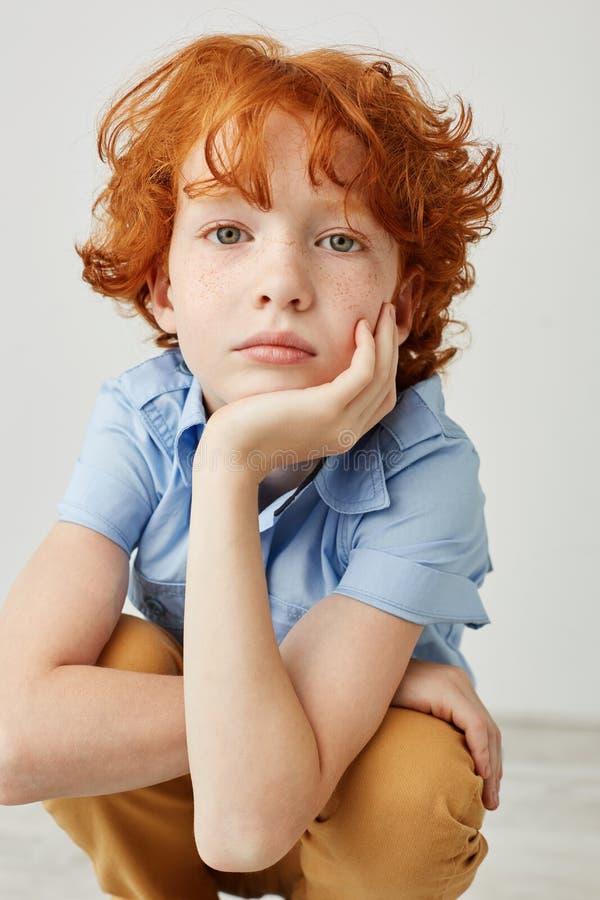 Verticale dicht omhoog geschoten van grappige jongen met oranje haar en sproeten, houdend hoofd met hand, die in camera met rust  stock afbeeldingen