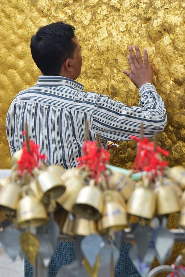 Verticale dichte omhooggaande mening van Pelgrim die zorgvuldig gouden folies op gouden rots kleven bij de Kyaiktiyo-Pagode met r stock fotografie