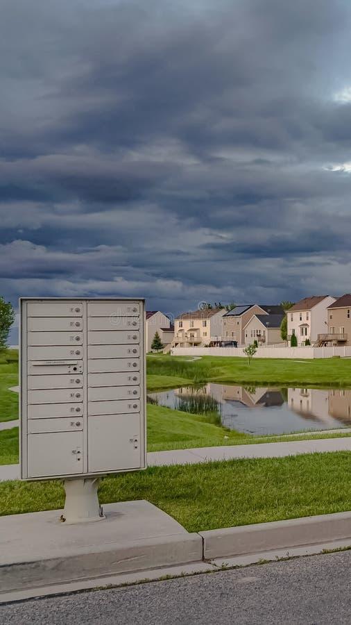Verticale die Hemel met grijze wolken over huizen en vijver amid een enorm grasrijk terrein wordt gevuld royalty-vrije stock afbeelding