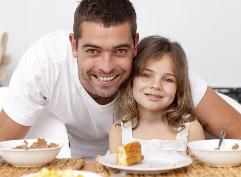 Verticale du père et du descendant prenant le petit déjeuner images libres de droits