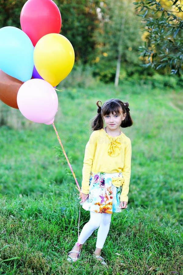 Verticale extérieure de petite fille avec des ballons image stock