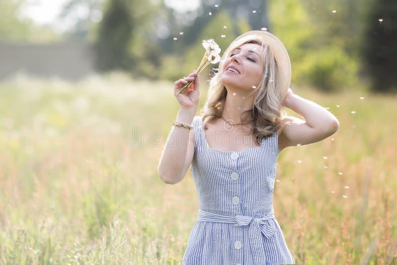 Verticale femelle ? l'ext?rieur une femme dans un chapeau de paille dans un domaine de fleur avec un bouquet des fleurs sauvages photographie stock