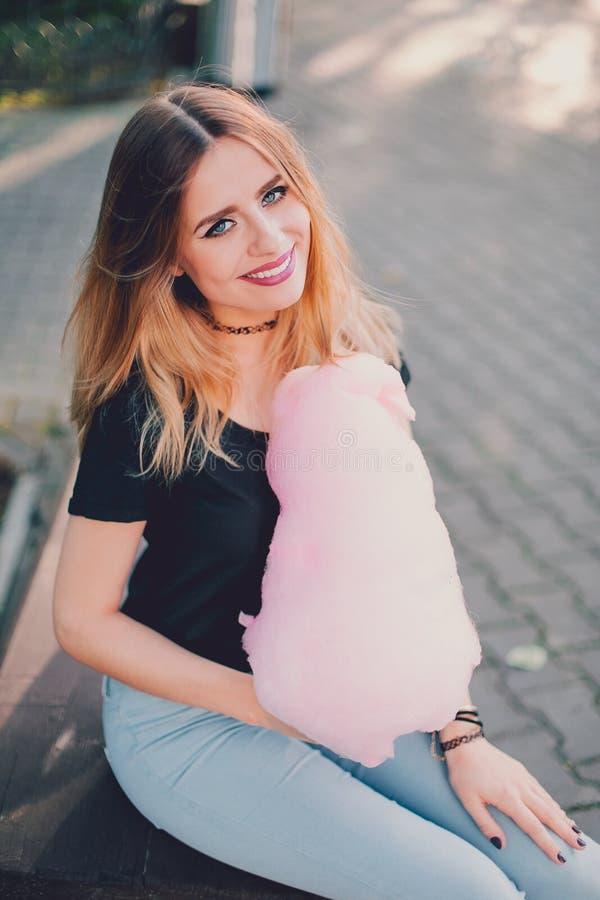 Verticale foto Het glimlachen hipster meisjeszitting op de bank in park met gesponnen suiker royalty-vrije stock afbeeldingen