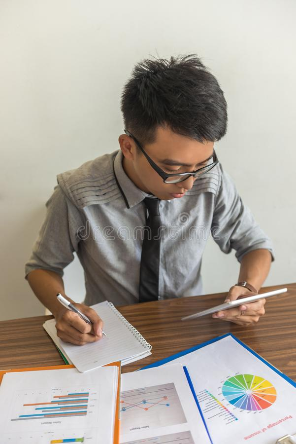 Verticale foto van de jonge bureaumens die tablet gebruiken royalty-vrije stock afbeeldingen