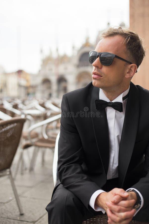 Verticale foto van de jonge knappe mens in smokingzitting in openluchtkoffie royalty-vrije stock foto