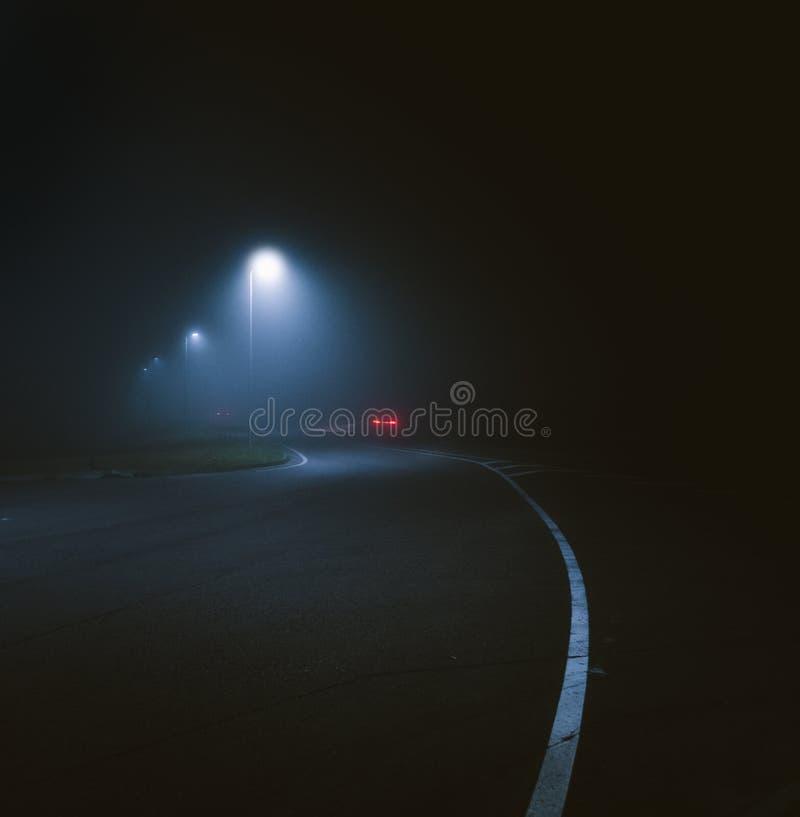 Verticale foto van een advertentie van de lamp bij de straat die 's nachts werd vastgelegd stock fotografie