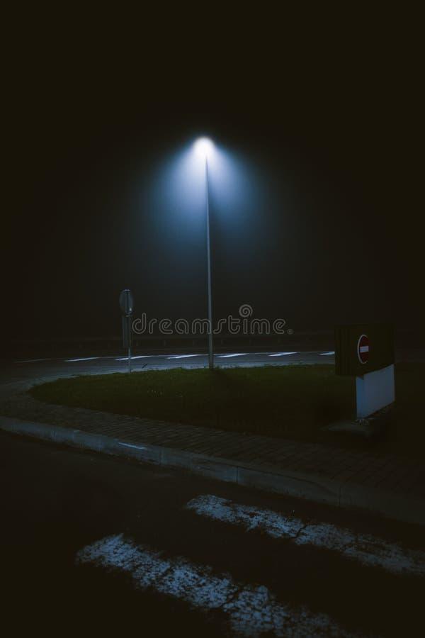 Verticale foto van een advertentie van de lamp bij de straat die 's nachts werd vastgelegd stock afbeelding