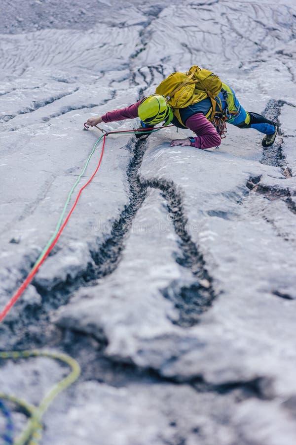 Verticale foto van een persoon die een rots in de Alpen in Oostenrijk beklimt - het omgaan met het concept uitdagingen stock afbeeldingen