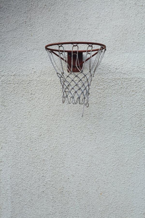 Verticale foto van een rode basketbalhoepel op een vuile witte muur overdag stock afbeelding